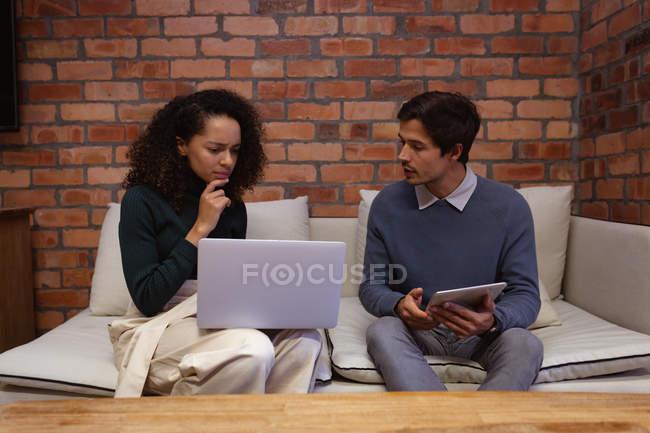 Vista frontal de cerca de una joven mujer de raza mixta y un joven hombre caucásico usando una computadora portátil y una tableta y teniendo una discusión sentada en un sofá en la sala de estar de una oficina creativa - foto de stock