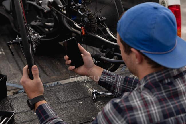 Заднього огляду крупним планом молодого Кавказького людини в інвалідному візку приймаючи лежачий велосипед з задньої частини автомобіля і за допомогою свого смартфона — стокове фото
