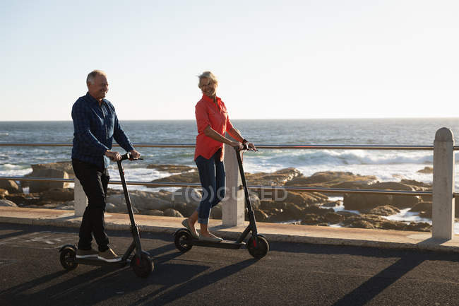 Opinião dianteira uma equitação caucasiano madura do homem e da mulher e scooters pelo mar no por do sol — Fotografia de Stock