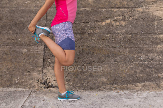 Side view low section of woman wearing sports clothes standing in front of a wall in a street, holding her foot and stretching her leg during a workout — Stock Photo