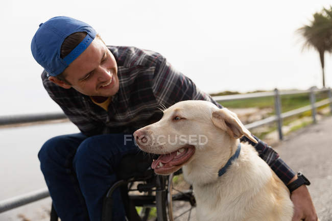 Вид спереду крупним планом молодого Кавказького чоловіка в інвалідному візку приймаючи прогулянку зі своєю собакою в сільській місцевості, посміхаючись — стокове фото