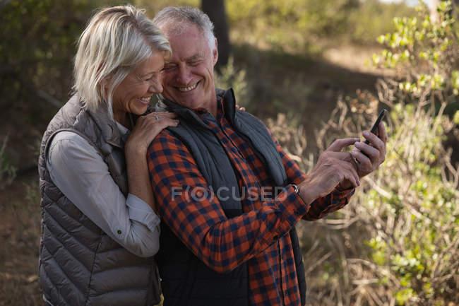 Боковой вид зрелого белого мужчины и женщины, улыбающихся и делающих селфи в сельской местности — стоковое фото