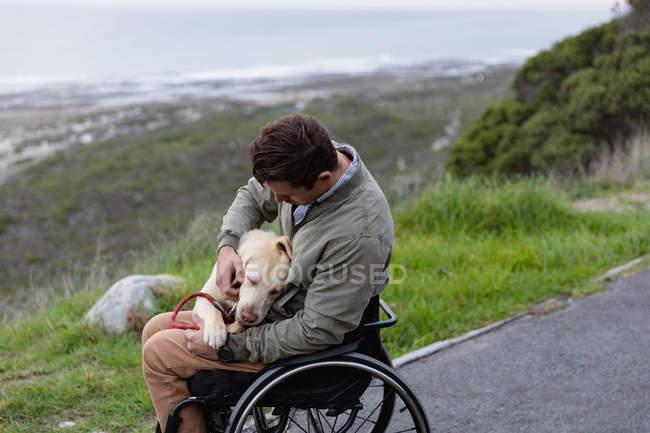 Vue latérale d'un jeune homme caucasien en fauteuil roulant se promenant avec son chien à la campagne au bord de la mer, caressant le chien sur ses genoux — Photo de stock