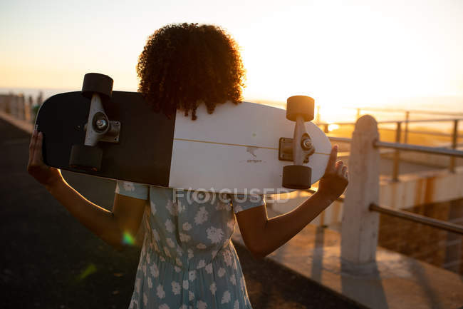 Rear view close up of young mixed race woman holding a skateboard on her shoulders admiring the view by the sea, backlit by the setting sun — Stock Photo