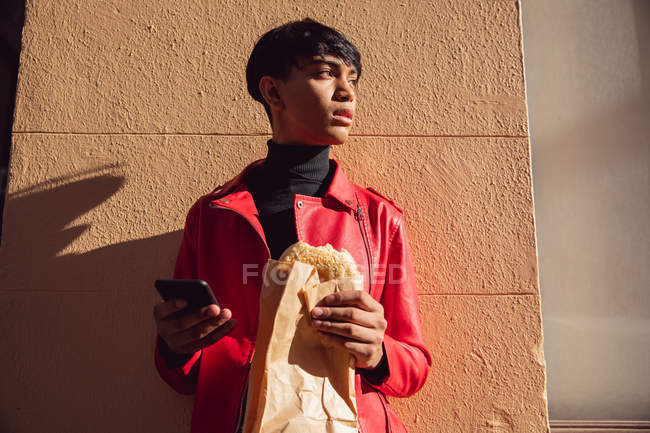 Side view of a fashionable young mixed race transgender adult in the street, using a smartphone and eating a sandwich — Stock Photo