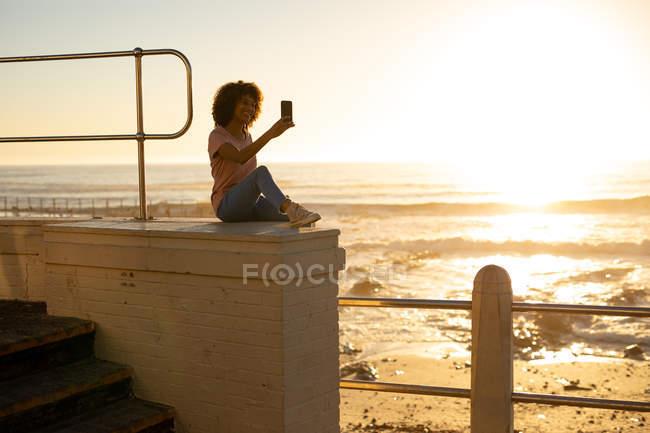 Вид сбоку молодой женщины смешанной расы, делающей селфи, сидящей на стене на закате у моря — стоковое фото