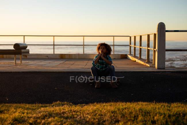 Vista frontale di un ragazzo pre-adolescente seduto su uno skateboard al tramonto in riva al mare — Foto stock