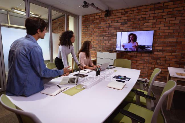 Seitenansicht einer jungen Frau mit gemischter Rasse und einer jungen kaukasischen Frau und einem Mann, die im Büro eines kreativen Unternehmens arbeiten, bei einem Treffen mit einer Kollegin, die per Videolink kommuniziert, sichtbar auf einem wandmontierten Bildschirm — Stockfoto