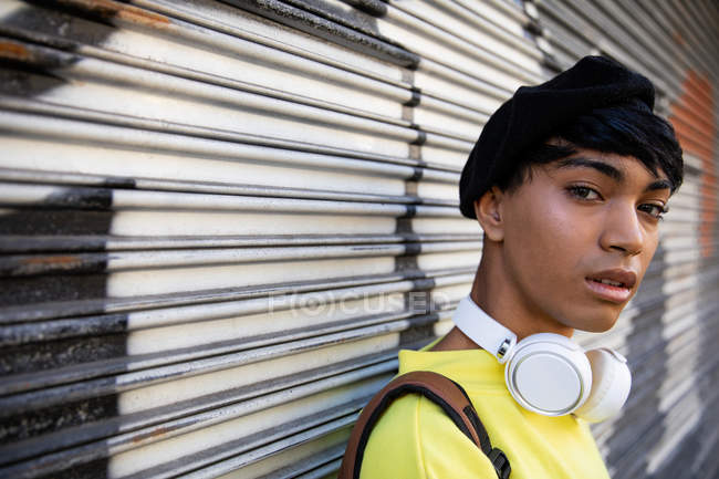 Ritratto di un giovane transgender transgender di moda per strada, con un basco con dei graffiti sullo sfondo — Foto stock