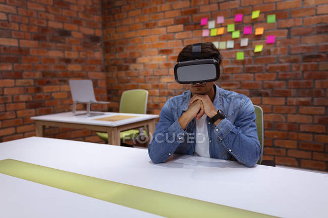 Front view of a young Caucasian man sitting at a desk wearing a VR headset with his chin resting on his hands, in the office of a creative business — Stock Photo