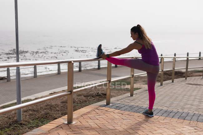 Вид сбоку молодой белой женщины в спортивной одежде, опирающейся на забор, растягивающей ногу во время тренировки в солнечный день у моря — стоковое фото