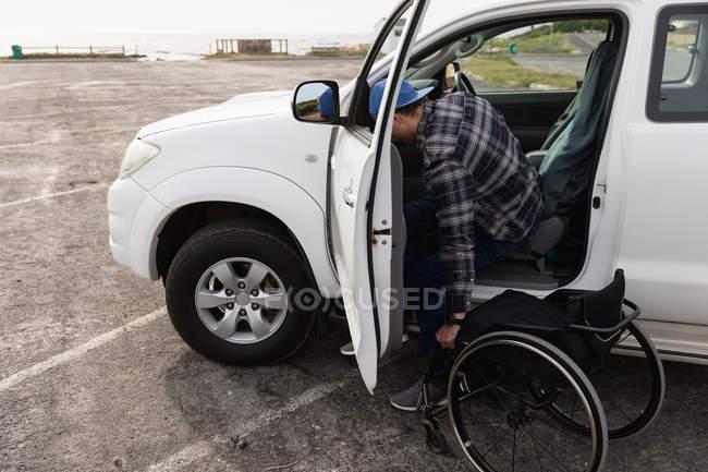 Вид збоку молодого Кавказького чоловіка вихід з машини в інвалідному візку на автостоянці біля моря — стокове фото