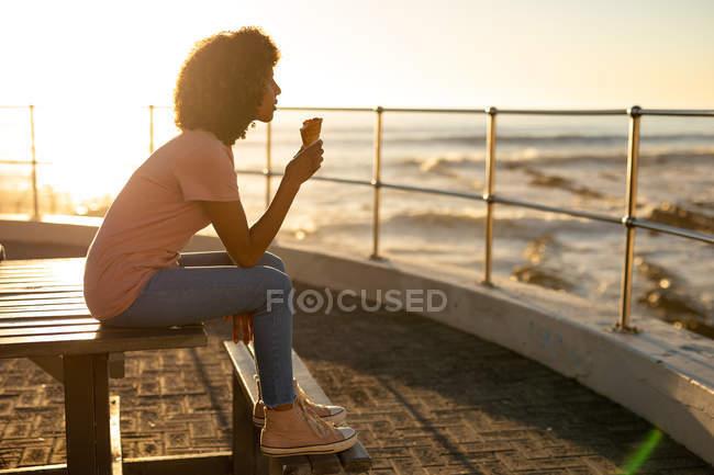 Vue latérale d'une jeune femme métissée assise sur un banc mangeant une glace et admirant la vue au coucher du soleil sur la mer — Photo de stock