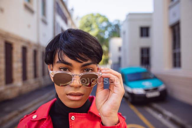 Портрет модний молодий змішаної раси транссексуалів дорослий на вулиці, беручи сонцезахисні окуляри від — стокове фото