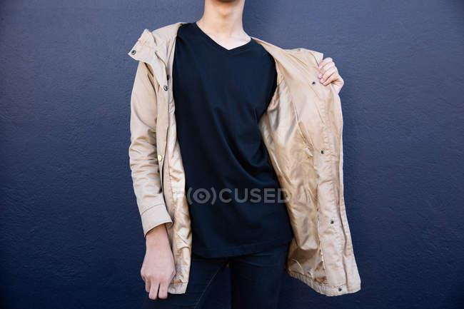 Вид спереди на модного человека на улице у серой стены — стоковое фото