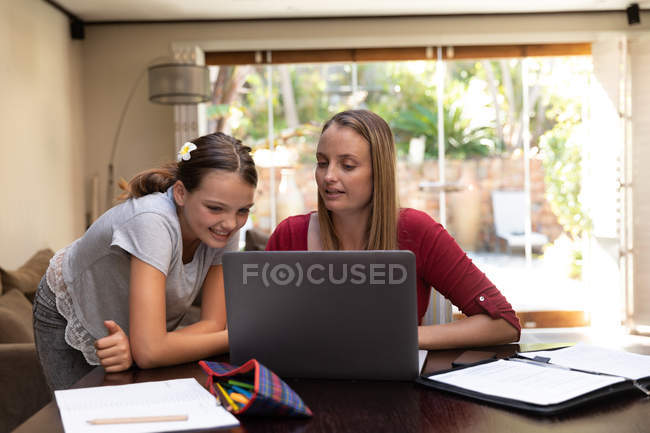 Front view of a young Caucasian woman using a laptop computer with her tween daughter looking on, in their dining room — Stock Photo