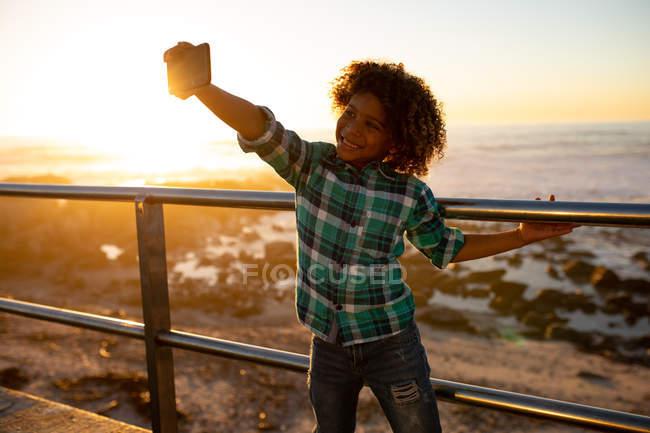 Vista frontale di un adolescente sorridente che tiene in mano uno smartphone e si fa un selfie aggrappato ad una balaustra ad un tramonto in riva al mare — Foto stock