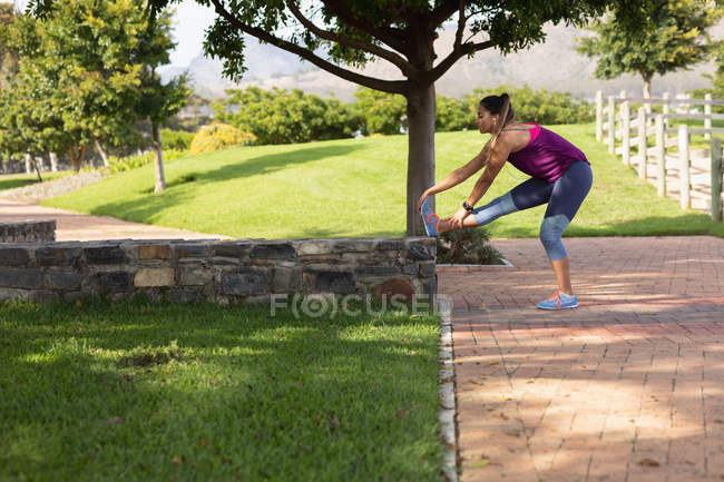 Side view of a young Caucasian woman wearing sports clothes touching her toes with her leg up on a low wall during a workout in a park — Stock Photo