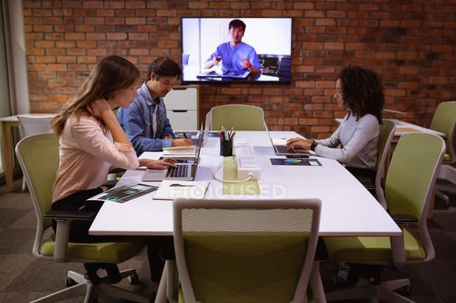 Бічний погляд на молоду змішану расу і молоду кавказьку жінку і чоловіка, які працюють в офісі творчого бізнесу.. — стокове фото