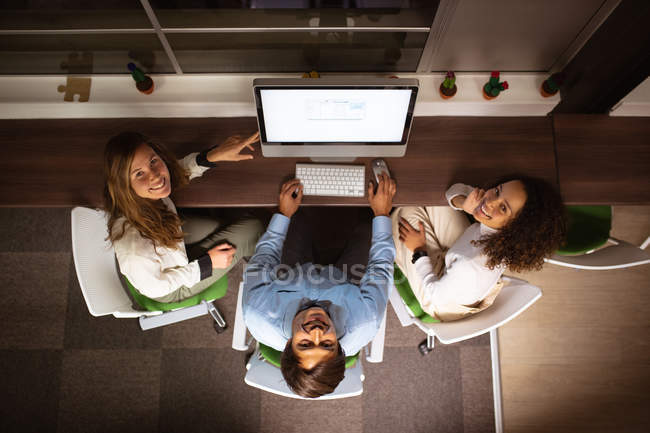 Overhead view of a young mixed race woman and a young Caucasian woman and man sitting at a table around a computer monitor together, looking up to camera and smiling, in the office of a creative business — Stock Photo