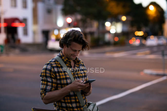 Side view of a young Caucasian man texting standing in a city street during his evening commute — Stock Photo