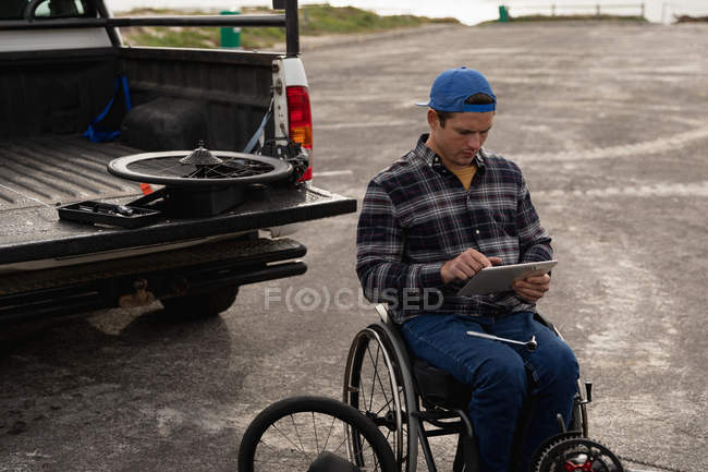 Front view of a young Caucasian man in a wheelchair assembling a recumbent bicycle and using a tablet in a car park by the sea — Stock Photo