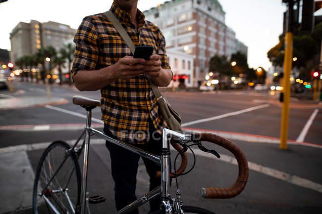 Vue de face au milieu d'un jeune homme caucasien debout à côté d'un vélo et utilisant un smartphone debout dans une rue animée de la ville le soir — Photo de stock