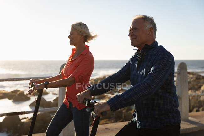 Side view close up of a mature Caucasian man and woman riding e scooters by the sea at sunset — Stock Photo