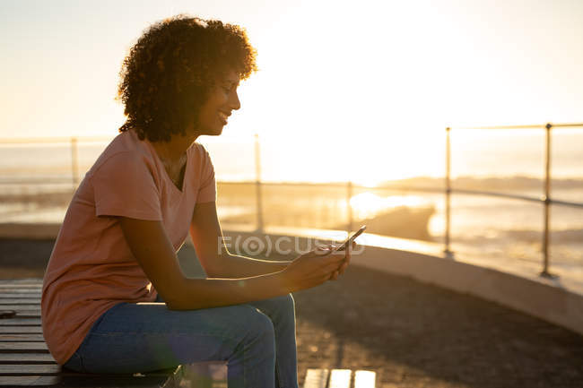 Вид сбоку на улыбающуюся молодую женщину смешанной расы с помощью смартфона, сидящую на скамейке на закате у моря — стоковое фото