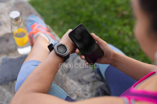 Над плечі жінка, що носить спортивний одяг перевірка її смарт-годинник і смартфон під час роботи в парку — стокове фото