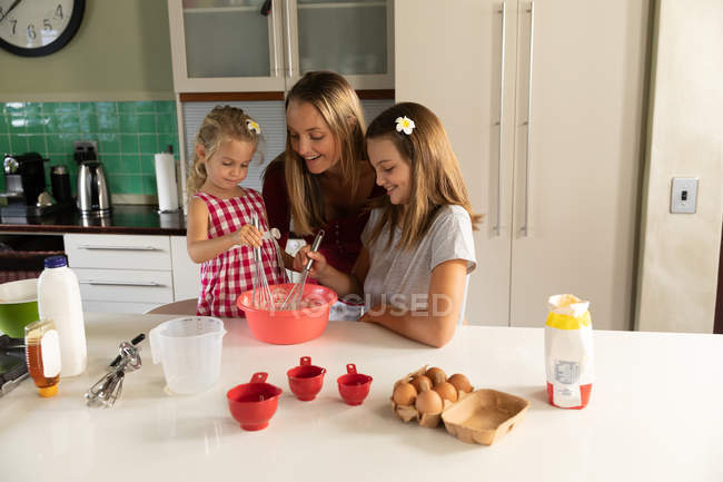 Front view of a young Caucasian woman cooking with her tween and younger daughters in their kitchen — Stock Photo