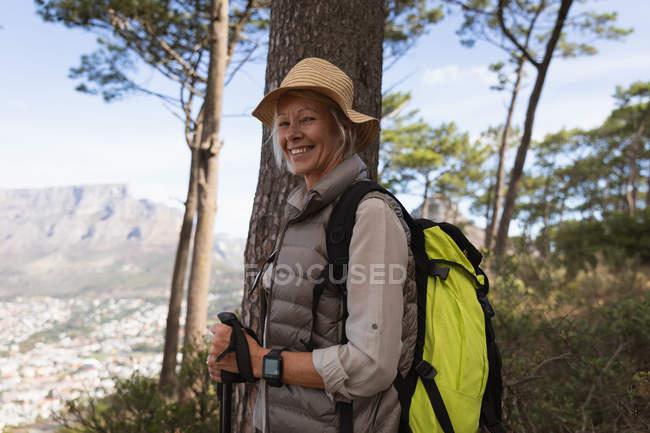 Ritratto di una donna caucasica matura che tiene bastoni da nordic walking e sorride alla telecamera, con campagna alle spalle — Foto stock