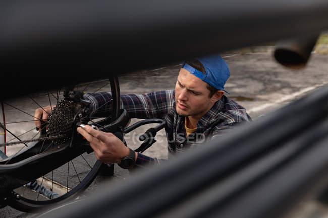Вид збоку крупним планом молодого Кавказького чоловіка в інвалідному візку, складання лежачого велосипеда в автостоянці — стокове фото