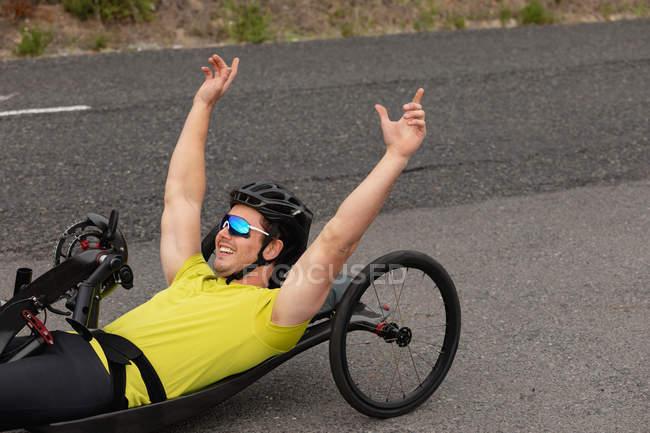 Вид збоку крупним планом молодого Кавказького людини в спортивному одязі на лежачому велосипеді на велосипеді по дорозі, Усміхаючись руками в повітрі — стокове фото