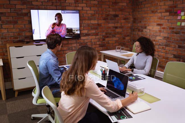 Vue de côté d'une jeune femme métissée et d'une jeune femme et homme caucasiens travaillant sur des ordinateurs portables dans le bureau d'une entreprise créative. Un collègue masculin est visible sur un écran mural, communiquant par liaison vidéo — Photo de stock