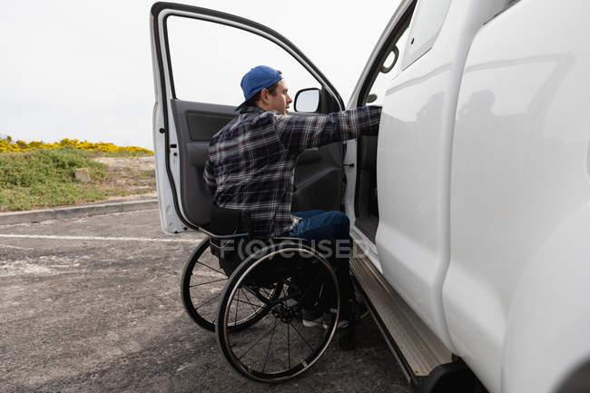 Вид збоку молодого Кавказького чоловіка в інвалідному візку на його машині, припаркованого в автостоянці з відкритими дверима — стокове фото