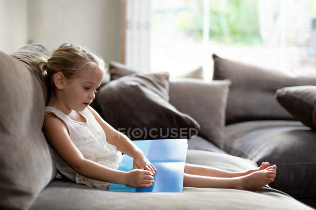 Side view of a young Caucasian girl sitting on a sofa reading a book in her sitting room — Stock Photo