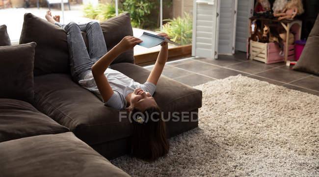 Передний вид юной белой девушки, читающей в гостиной — стоковое фото