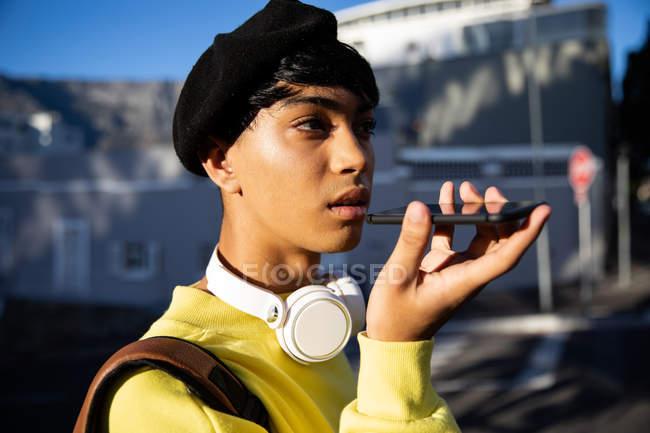 Вид збоку модного молодого змішаного гонки транссексуалів дорослий на вулиці, говорячи на смартфон носіння бере — стокове фото