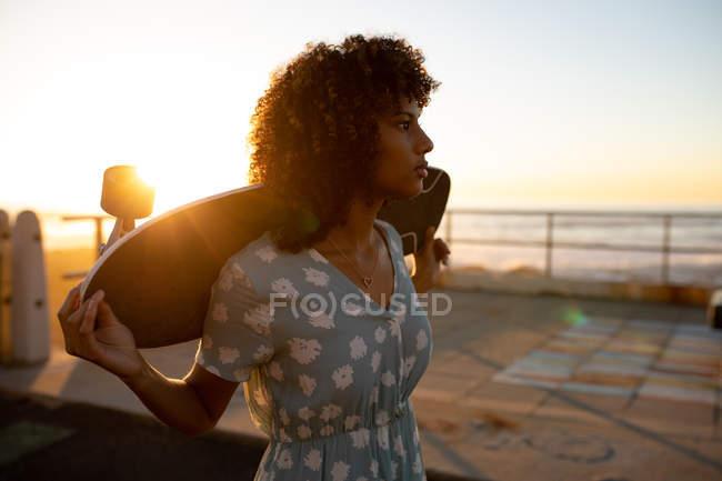 Vista laterale da vicino della giovane donna di razza mista che tiene uno skateboard sulle spalle ammirando la vista sul mare, retroilluminata dal sole al tramonto — Foto stock
