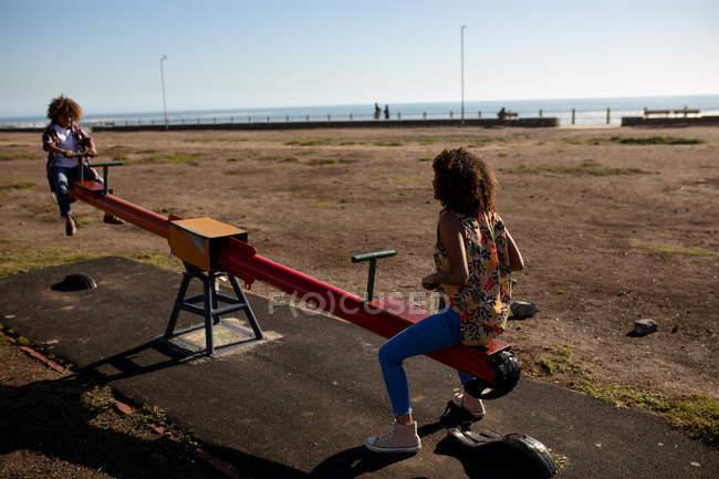 Vista frontale di una giovane donna di razza mista e suo figlio pre-adolescente godendo tempo insieme giocare in un parco giochi, seduto su un'altalena in una giornata di sole — Foto stock
