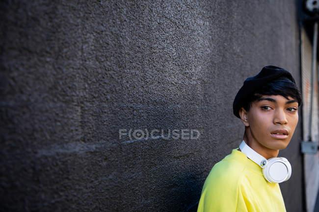 Вид на модний молодий змішаних раси транссексуалів дорослий на вулиці, проти сірої стіни — стокове фото
