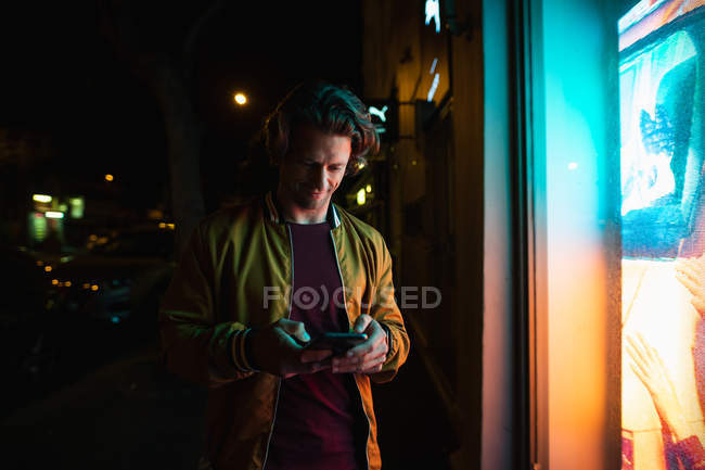 Front view of a smiling young Caucasian man standing by a shop window at night using a smartphone — Stock Photo