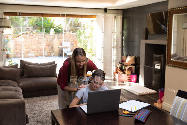 Front view of a young Caucasian pregnant woman standing behind her tween daughter using a laptop computer in their dining room — Stock Photo