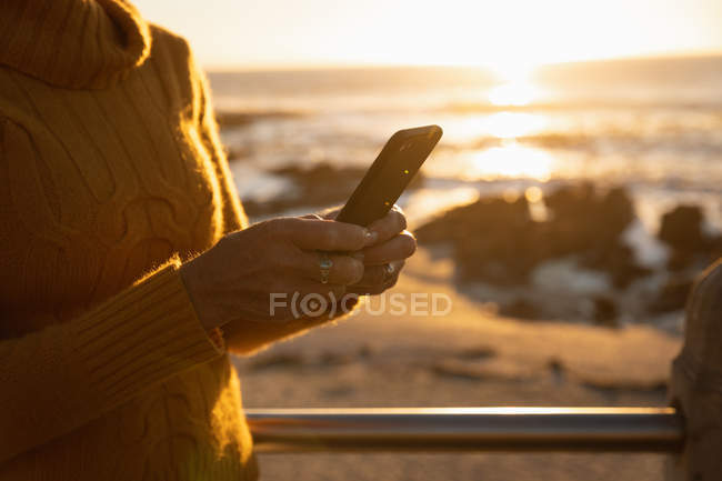Side view close up of woman using a smartphone by the sea at sunset — Stock Photo