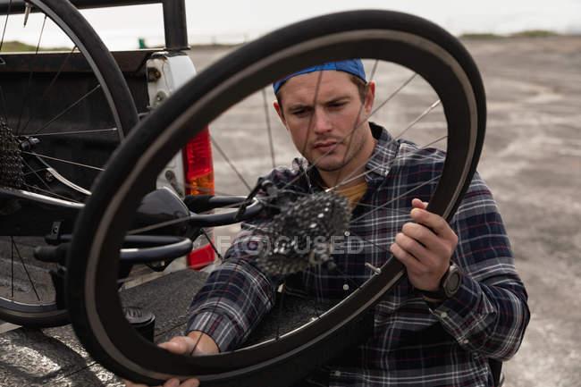 Вид спереду крупним планом молодого Кавказького чоловіка в інвалідному візку приймаючи лежачий велосипед з задньої частини своєї машини, щоб зібрати його, тримаючи колесо на автостоянці біля моря — стокове фото