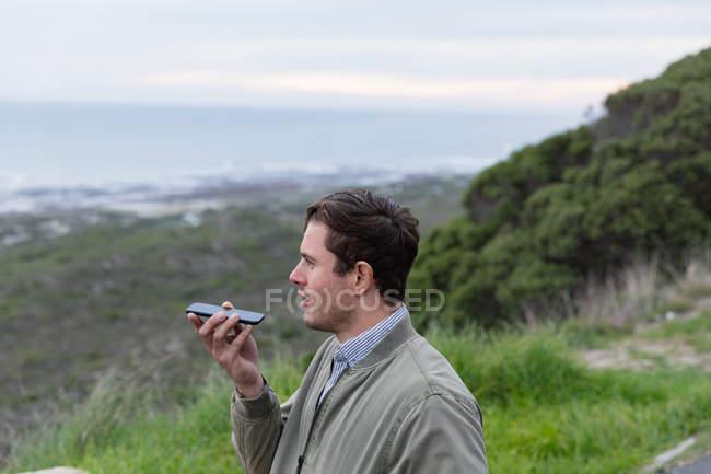 Вид сбоку на молодого кавказца, наслаждающегося днем в сельской местности у моря, разговаривающего по смартфону — стоковое фото