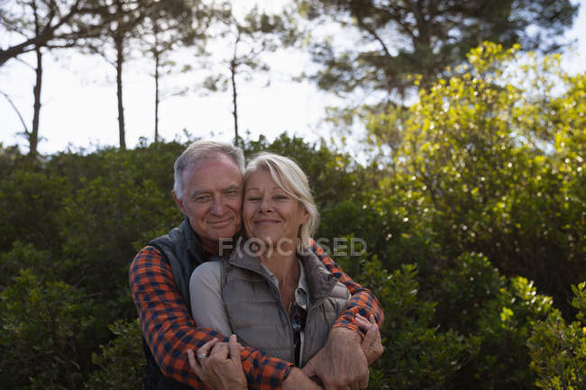 Portrait of a mature Caucasian man and woman embracing and smiling to camera during a walk in a rural setting — Stock Photo