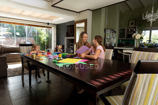 Front view of a young Caucasian woman doing crafts with her tween and younger daughters in their sitting room — Stock Photo