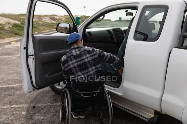 Заднього виду молодого Кавказького чоловіка в інвалідному візку його пікап, припаркованого в автостоянці з відкритими дверима — стокове фото
